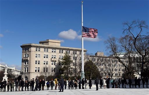 The flag flies at half staff in honor of Justice Antonin Scalia, as members of the public arrive to visit the Supreme Court in Washington, Wednesday, March 2, 2016, as anti-abortion and pro-abortion rights protesters rally outside the court. The abortion