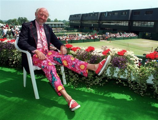 In this June 30, 1993, file photo, NBC tennis commentator Bud Collins displays a pair of brightly-colored trousers as he sits overlooking the outside courts at Wimbledon, England.