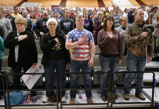 Wichita, Kan., residents prepare for the pledge allegiance at a caucus site, Saturday, March 5, 2016, in Wichita.