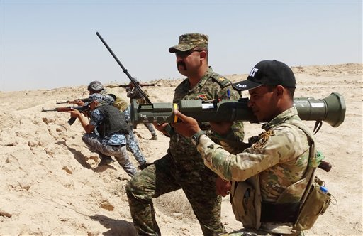 In this Thursday, July, 23, 2015 file photo, Iraqi Army soldiers with new U.S.-made weapons take combat positions at the front line in an eastern suburb of Ramadi, backed by Shiite and Sunni pro-government fighters and U.S.-led coalition airstrikes again