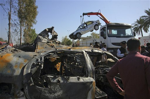 Civilians and security forces gather as municipality workers remove destroyed vehicles at the scene of a suicide bomb attack in Hillah, about 60 miles (95 kilometers) south of Baghdad, Iraq, Sunday, March 6, 2016. A suicide bomber on Sunday rammed his exp