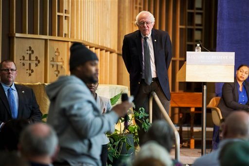 In this Feb. 25, 2016 file photo, Democratic presidential candidate, Sen. Bernie Sanders, I-Vt. listens to concerns about contaminated water during a community forum at Woodside Church in Flint, Mich. Flint, a majority-black impoverished community in a s