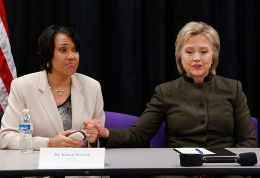 In this Feb. 7, 2016 file photo, Democratic presidential candidate Hillary Clinton holds the hand of Flint Mayor Karen Weaver during a meeting with officials at the House Of Prayer Missionary Baptist Church in Flint, Mich. Flint, a majority-black impoveri