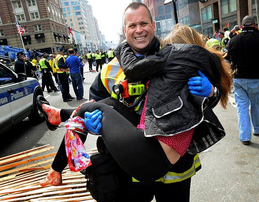 In this April 15, 2013 file photo, Boston Firefighter James Plourde carries Victoria McGrath from the scene after a bombing near the Boston Marathon finish line.