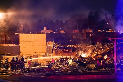 Firefighters work at the scene of a building explosion in Seattle's Greenwood neighborhood early Wednesday, March 9, 2016.