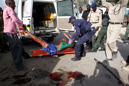 Somali police officers carry a suspected suicide car bomber wounded in a bombing outside a police academy in Mogadishu, Somalia, Wednesday, March 9, 2016. A Somali police official said three police officers and one civilian have been killed in the car bom