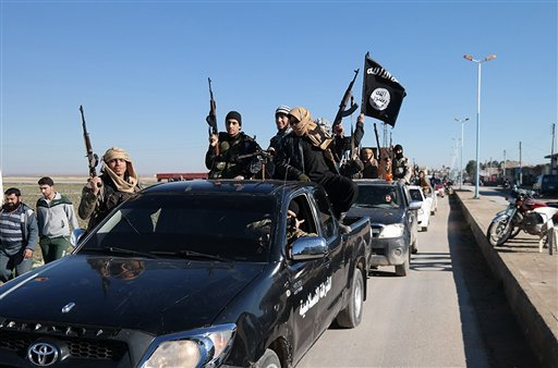 FILE - In this this file photo released on May 4, 2015, on a militant website, which has been verified and is consistent with other AP reporting, Islamic State militants pass by a convoy in Tel Abyad, northeast Syria.