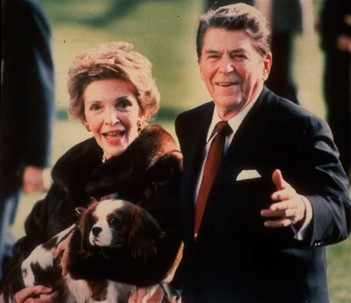 FILE - This December 1986, file photo shows first lady Nancy Reagan holding the Reagans' pet Rex, a King Charles spaniel, as she and President Reagan walk on the White House South lawn.