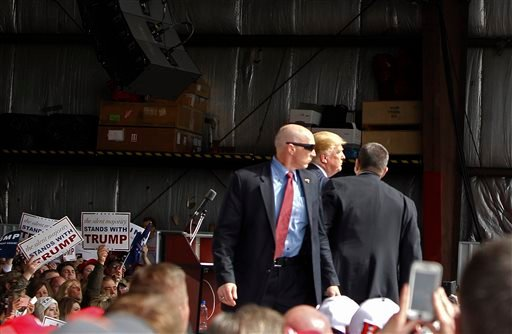 Secret Service agents guard Republican presidential candidate, businessman Donald Trump, on the stage after a man tried to breach the security buffer at his campaign event at the Wright Brothers Aero Hangar Saturday, March 12, 2016, in Vandalia, Ohio.