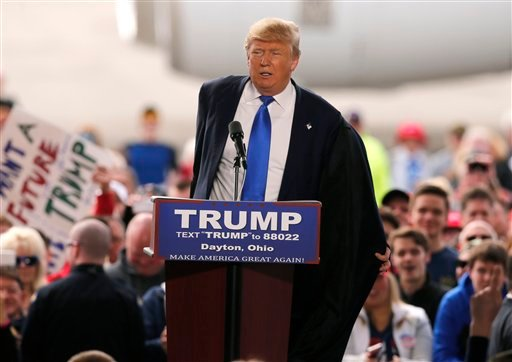 Republican presidential candidate, businessman Donald Trump, takes his coat off as he speaks at the Wright Brothers Aero Hangar during a rally, Saturday, March 12, 2016, in Vandalia, Ohio.