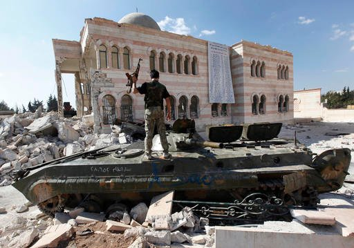 In this file photo taken on Sept. 23, 2012, a Free Syrian Army soldier stands on a damaged Syrian military tank in front of a damaged mosque, which were destroyed during fighting with government forces, in the Syrian town of Azaz, on the outskirts of Alep