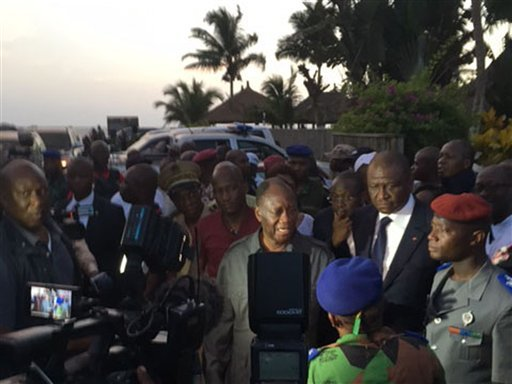 Ivory Coast's President Alassane Ouattara, center, visits the area were gunmen attacked people in Grand Bassam, Ivory Coast, March 13, 2016. At least six armed men attacked beachgoers outside three hotels Sunday in Grand-Bassam, killing several civilians
