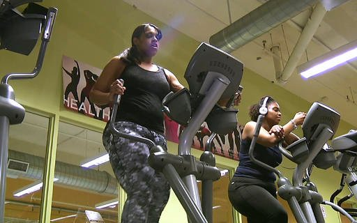 In this Feb. 1, 2016 still photo from video, Monisha Long, left, works on a elliptical machine in Boston's Dorchester neighborhood.