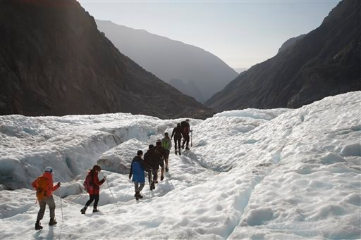 In this Feb. 6, 2016 photo, tourists who have taken a helicopter trip onto the Fox Glacier follow a guide in New Zealand. The Fox and Franz Josef glaciers have been melting at such a rapid rate that it has become too dangerous for tourists to hike onto th