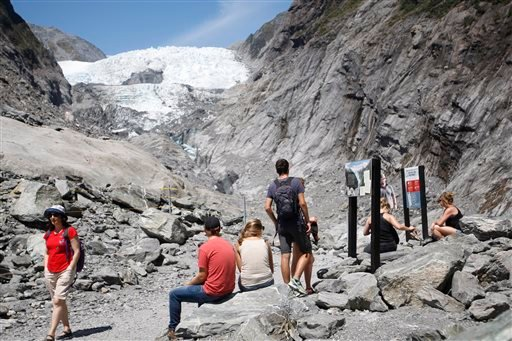 In this Feb. 6, 2016 photo, tourist relax at the end of the track at the Franz Josef Glacier in New Zealand. The Fox and Franz Josef glaciers have been melting at such a rapid rate that it has become too dangerous for tourists to hike onto them from the v
