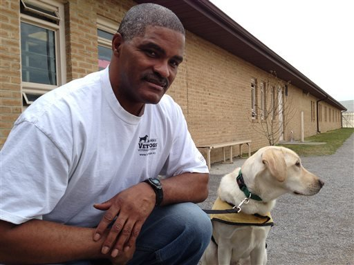 March 10, 2016 photo: Lee Dorsey, an inmate at the Maryland Correctional Institution-Hagerstown, poses for a photo with River he is training for America's VetDogs, while at the prison yard in Hagerstown, Md. (AP Photo/David Dishneau)
