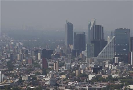 Haze hangs over Mexico City at midday, Tuesday, March 15, 2016. The Mexico City government declared its first air pollution alert in 11 years Monday after ozone levels reached almost twice the acceptable limit.(AP Photo/Rebecca Blackwell)