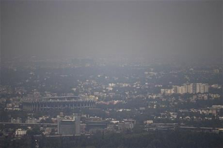 Mexico City's Azteca Stadium, left, is seen through a thick haze, Tuesday, March 15, 2016. The Mexico City government declared its first air pollution alert in 11 years Monday, after ozone levels reached almost twice the acceptable limit. (AP Photo/Eduard