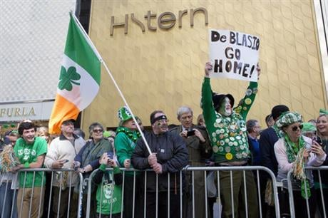 Dennis Dunn, who is originally from the Bronx borough of New York city holds up a sign as New York City Mayor Bill de Blasio marches up Fifth Avenue during the St. Patrick's Day parade, Thursday, March 17, 2016, in New York. (AP Photo/Mary Altaffer)