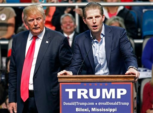 FILE - In this Jan. 2, 2016 file photo, Republican presidential candidate Donald Trump, left, listens as his son Eric Trump speaks during a rally in Biloxi, Miss.