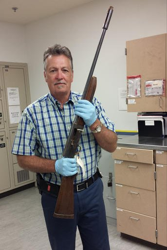 In this June 2015 photo released by the Seattle Police on Thursday, March 17, 2016, Detective Michael Ciesynski holds the shotgun which rock legend Kurt Cobain used to kill himself on April 8, 1994.