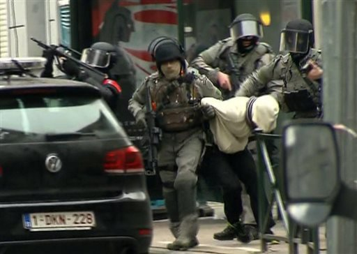 In this framegrab taken from VTM, armed police officers escort Salah Abdeslam to a police vehicle during a raid in the Molenbeek neighborhood of Brussels, Belgium, Friday March 18, 2016.