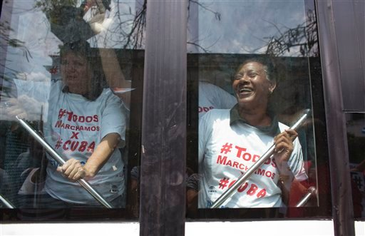 "Government supporters wearing shirts that read in Spanish: ""We all march for Cuba"" leave in a bus after staging a counter-protest to the weekly march by Ladies in White, a dissident women's group that calls for the release of political prisoners, in Havan"