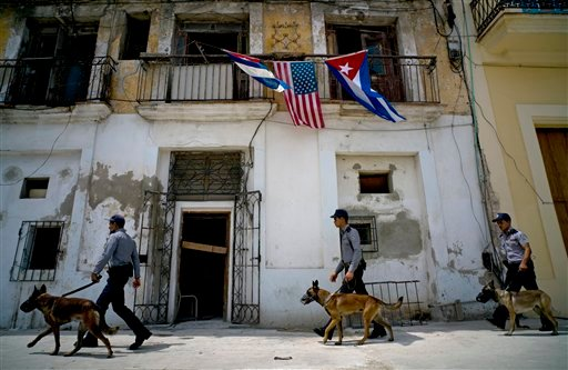 Under a balcony decorated with Cuban and US flags, Cuban police arrive to the area where President Barack Obama will visit upon arrival in Old Havana, Cuba, Sunday, March 20, 2016. In his historic visit to Cuba, Obama is relegating decades of American acr