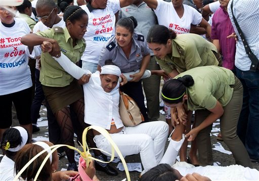 Policewomen drag away a member of Ladies in White, a women's dissident group that calls for the release of political prisoners, during their weekly protest in Havana, Cuba, Sunday, March 20, 2016. U.S. President Barack Obama arrives Sunday afternoon for a