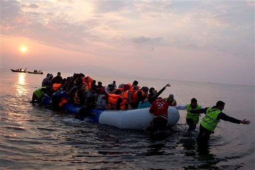 Volunteers help migrants and refugees on a dingy as they arrive at the shore of the northeastern Greek island of Lesbos, after crossing the Aegean sea from Turkey on Sunday, March 20, 2016. In another incident two Syrian refugees have been found dead on a