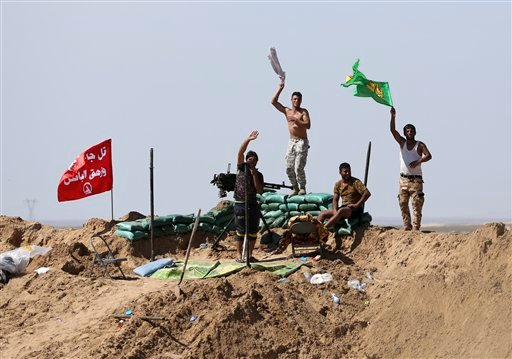 In this Wednesday, March 9, 2016 file photo, Popular Mobilization forces chant slogans against the Islamic State group as Iraqi Defense Minister Khaled al-Obeidi tours the front line in Anbar, Iraq. After months of losing ground in Iraq and Syria, the Is