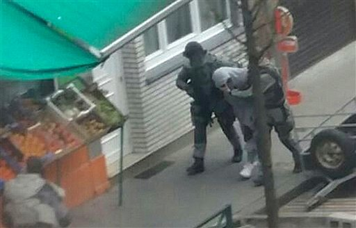 In this Friday, March 18, 2016 photo made available Monday March 21, an unidentified man believed to be connected to key suspect in the November 2015 Paris attacks Salah Abdeslam, is detained by police during a raid in the Molenbeek neighborhood of Brusse
