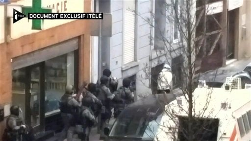 In this image taken from video made available on Monday March 21, 2016 a man believed to be Salah Abdeslam, right wearing white, the top suspect in the Paris attacks, runs from the police before being shot by the police during a raid in the Molenbeek neig