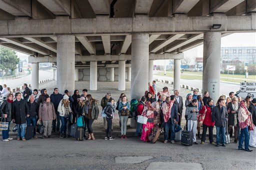 People stand near Brussels airport after being evacuated following explosions that rocked the facility in Brussels, Belgium, Tuesday March 22, 2016.
