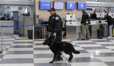 A K9 security officer and his dog walk through a terminal at O'Hare International Airport on Tuesday, March 22, 2016 in Chicago. The airport attack in Brussels highlights one of the most vulnerable stages of aviation security: the time travelers spend bet