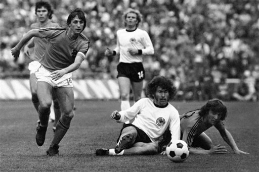 FILE - This is a July 7, 1974 file photo of Dutch forward Johan Cruyff, left, runs past German defender Paul Breitner, sitting on the pitch during the final of the Soccer World Cup at the Olympic Stadium in Munich, Germany.