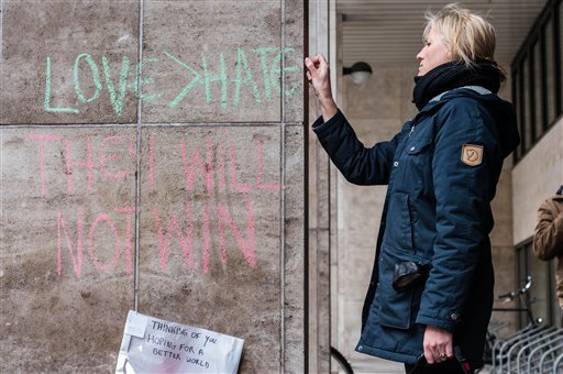A woman writes a solidarity message in chalk on the wall outside metro station Maelbeek in Brussels, Belgium, Thursday, March 24, 2016. Prosecutors announced a direct connection between the Brussels bombings and last year's attacks on Paris, which appear