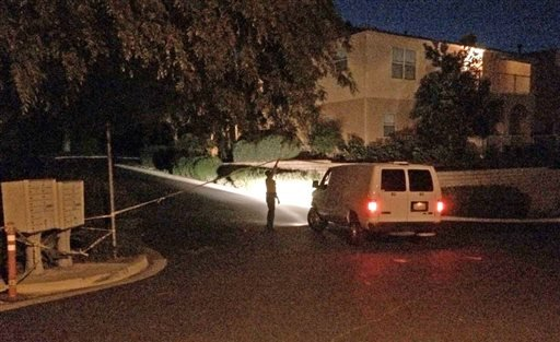 A sheriff's deputy lifts crime scene tape to allow a Coroner's Bureau van to proceed up Greenhill Way as the Santa Barbara County Sheriff's Office opened a homicide investigation after deputies discovered the remains of three people.