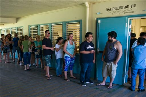 Voters line up outside a polling station set up at Kailua Intermediate School to register to vote in Hawaii's Democratic primary, Saturday, March 26, 2016, in Kailua, Hawaii. (AP Photo/Marco Garcia)