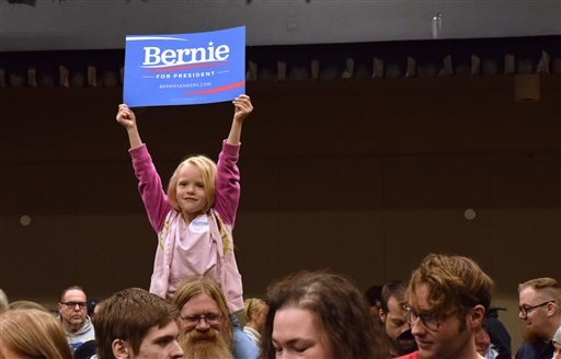 "Five-year-old Courtney Skinner holds up a ""Bernie Sanders for President"" sign while sitting on Tom Skinner's shoulders at the Juneau Democratic Caucus on Saturday, March 26, 2016, in Centennial Hall's Sheffield Ballroom in Juneau, Alaska. Sanders won Demo"