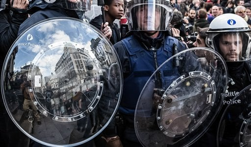 Riot police attend a memorial site during a protest by right wing demonstrators at the Place de la Bourse in Brussels, Sunday, March 27, 2016. In a sign of the tensions in the Belgian capital and the way security services are stretched across the country,