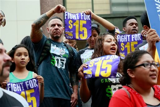 In this Tuesday, July 21, 2015 file photo, workers hold a rally in Los Angeles in support of the Los Angeles County Board of Supervisors' proposed minimum wage ordinance. (AP Photo/Nick Ut)