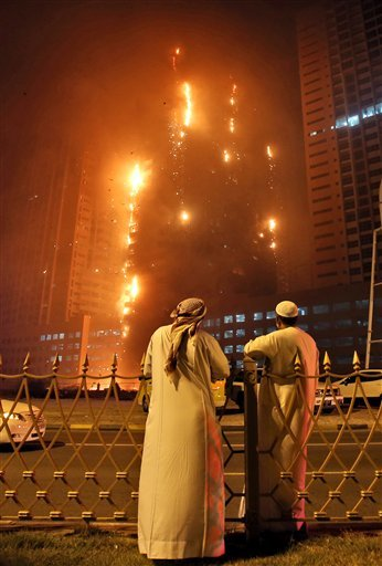Two Emirati officials as a fire spreads up the side of the watch a high-rise building in Ajman, United Arab Emirates, early Tuesday, March 29, 2016.