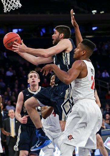 George Washington 's Patricio Garino (13) drives past San Diego State's Malik Pope (21) during the second half of an NCAA college basketball game in the semifinals of the NIT.