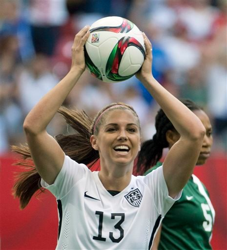 In this June 16, 2015, file photo, United States' Alex Morgan celebrates teammate Abby Wambach's goal as Nigeria's Onome Ebi looks on during the first half of a FIFA Women's World Cup soccer match in Vancouver, British Columbia, Canada.