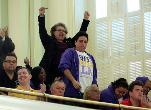 Supporters of a bill to raise California's minimum wage, celebrate in the Assembly gallery after the measure was approved by the state Assembly Thursday, March 31, 2016, in Sacramento, Calif.