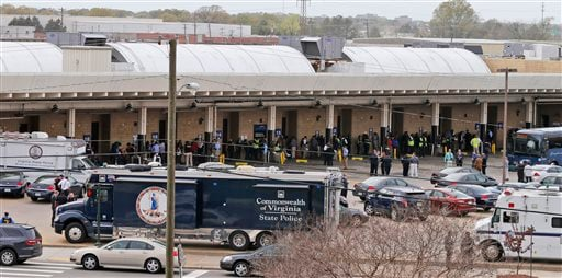 Police and rescue officials mingle with bus patrons outside the Greyhound Bus Station Thursday, March 31, 2016, in Richmond, Va. Virginia State Police say two troopers responding to a shooting at the Richmond bus station and a civilian have been taken to