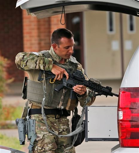 A law enforcement official stows his weapon after responding outside the Greyhound Bus Station Thursday, March 31, 2016 Richmond, VA. Virginia State Police said at least two troopers responding to a shooting at the Richmond bus station and civilian have b