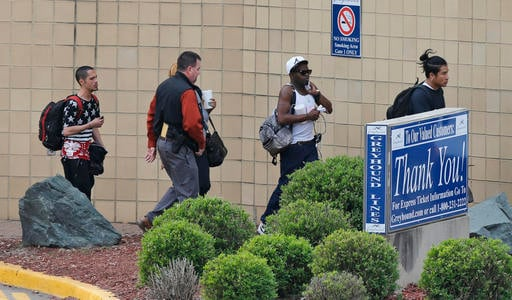 A group of bus patrons are escorted by a police officer outside the Greyhound Bus Station on Thursday, March 31, 2016, in Richmond, Va. Virginia State Police said at least two troopers responding to a shooting at the Richmond bus station and civilian have