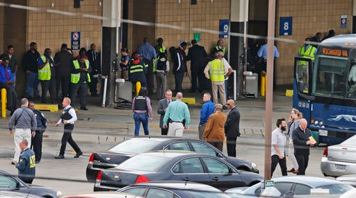 Police and rescue officials mingle with bus patrons outside the Greyhound Bus Station on Thursday, March 31, 2016, in Richmond, Va. Virginia State Police said at least two troopers responding to a shooting at the Richmond bus station and civilian have bee